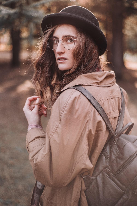 woman in brown leather jacket wearing black hat and black framed eyeglasses