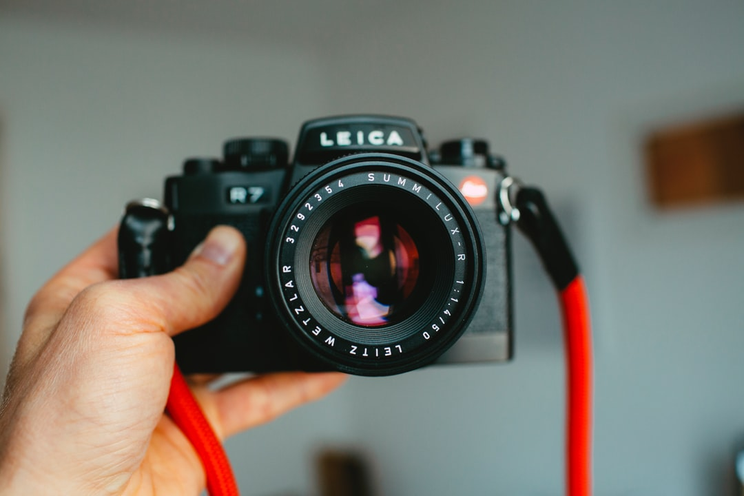 Vintage Classic Analog 35mm Photo Camera Leica R7 With Summilux 50mm 1.4 Prime Lens In Black With Red Rope - unsplash