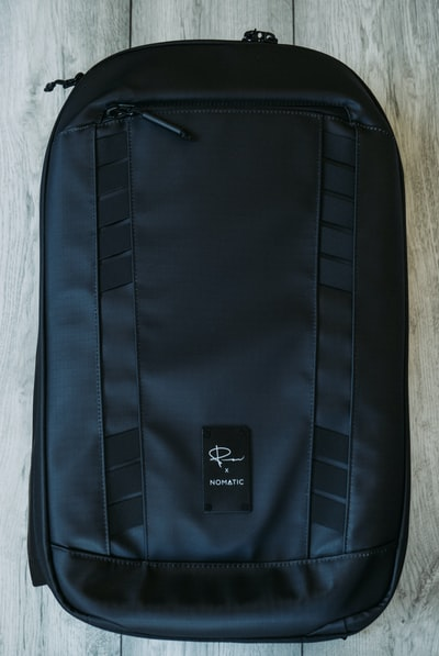 black and blue backpack on white textile