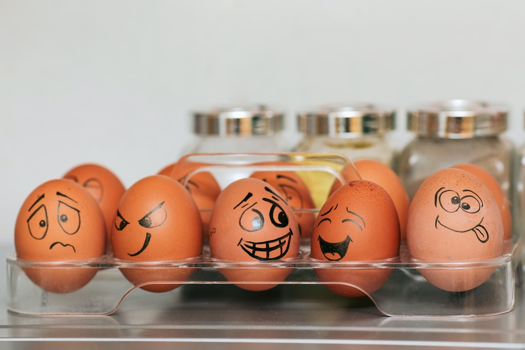 A photograph (wallpaper, picture) of eggs with different emotions against a background of blurred spices and a smooth gray wall.  Whole painted eggs in the kitchen, expressing a spectrum of emotions from sadness to joy or madness. Eggs with smile and crazy face.