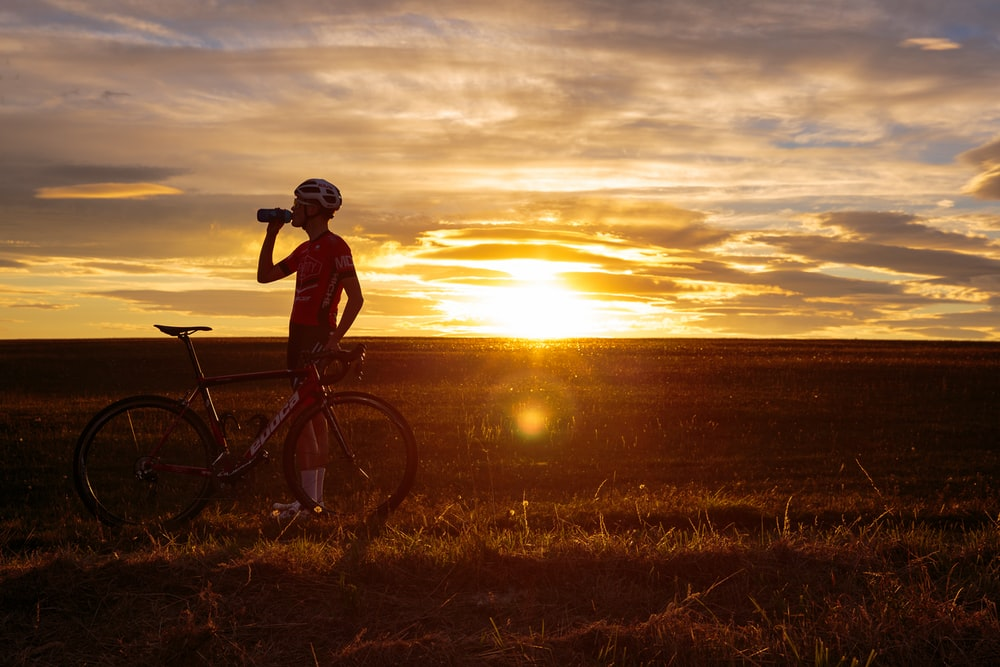 man riding bicycle on green grass field during sunset