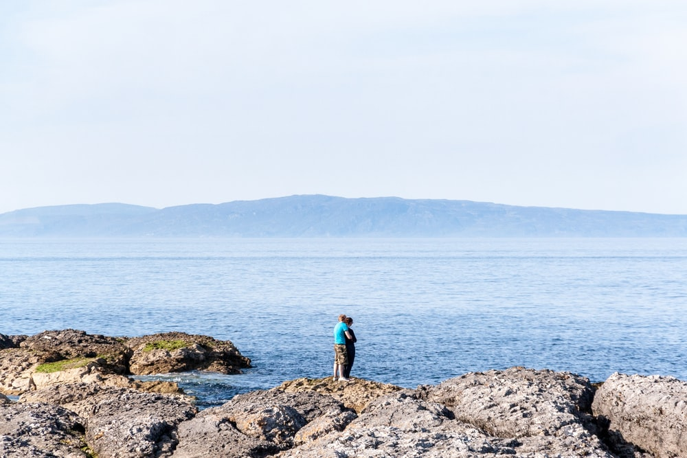 man in blue jacket standing on brown rock near body of water during daytime