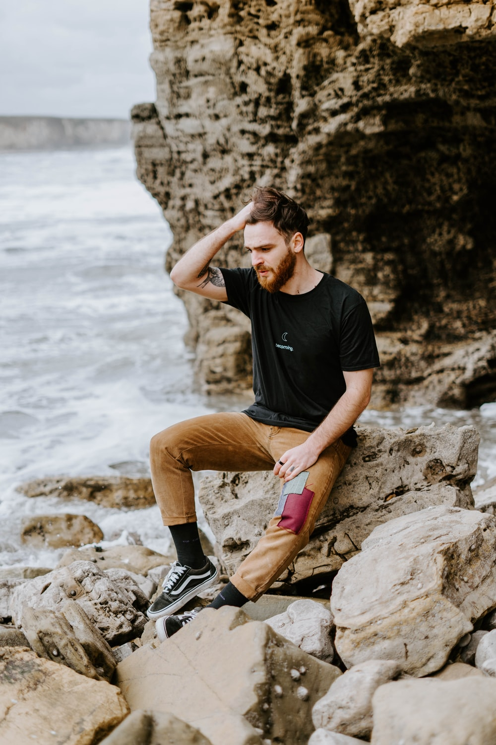 man in black t-shirt and brown shorts sitting on rock near body of water during