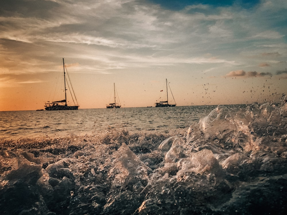 grayscale photo of sail boat on sea shore