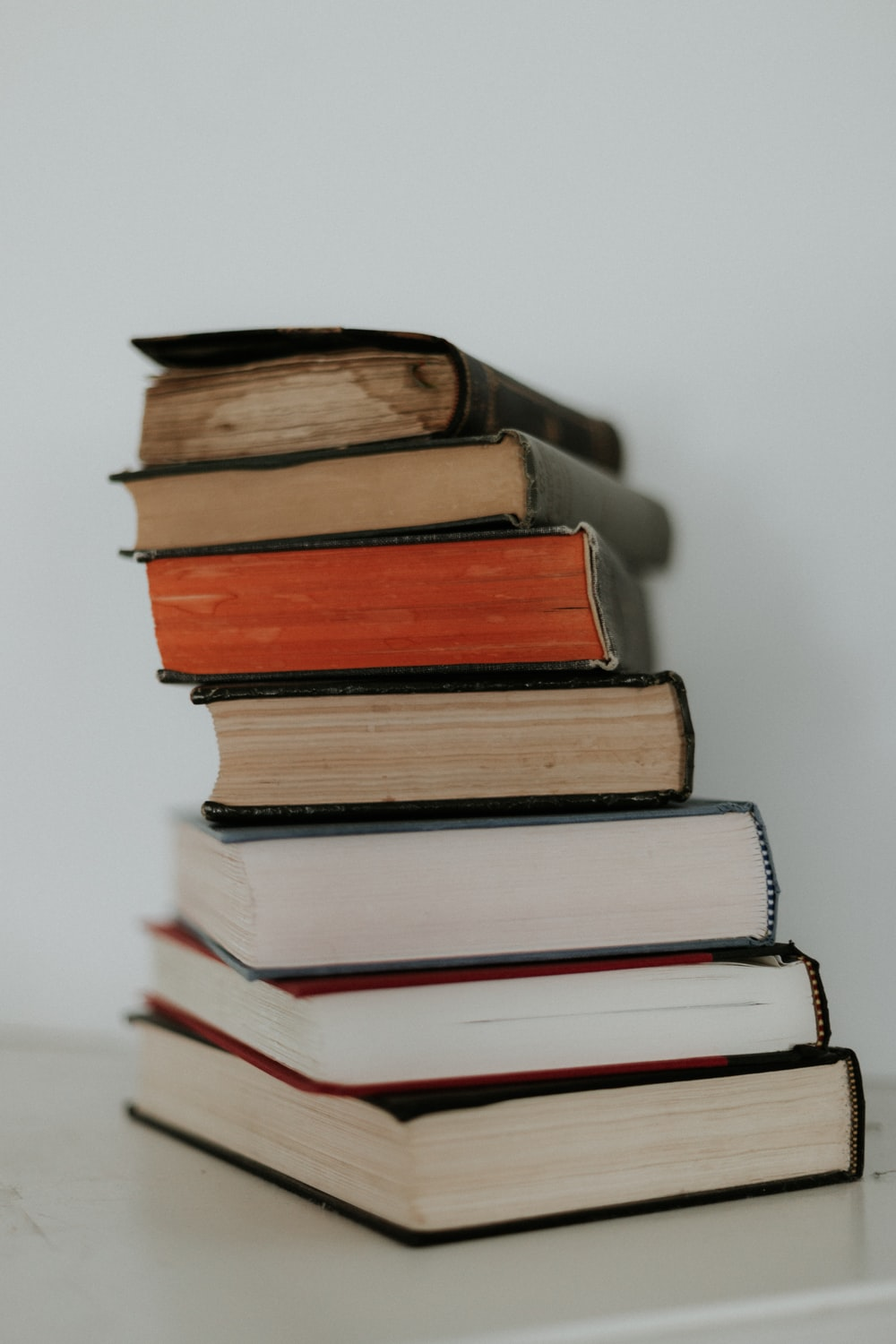 brown and red books on white surface
