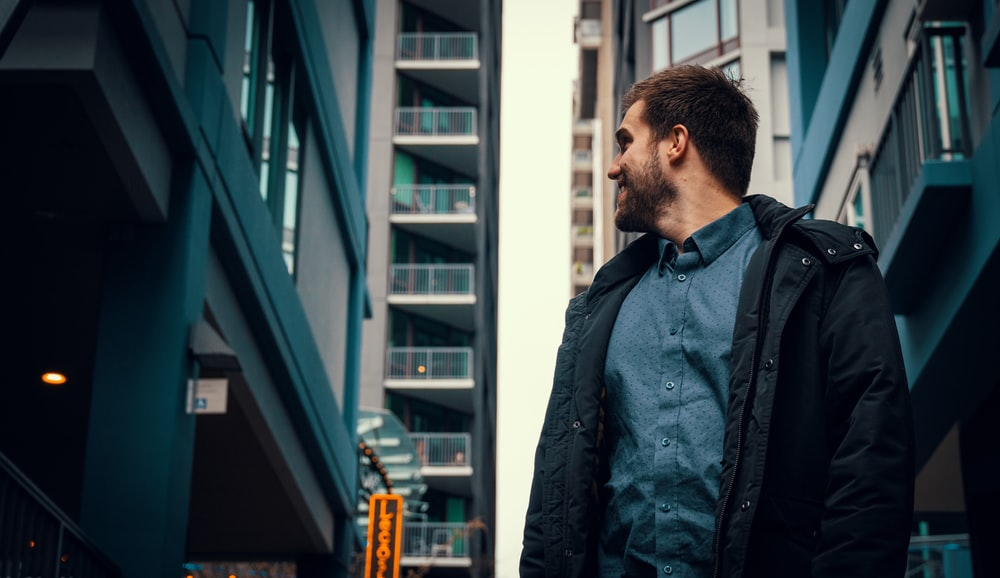 man in blue jacket standing near building during daytime