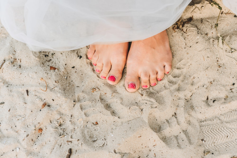 person with red pedicure standing on white textile