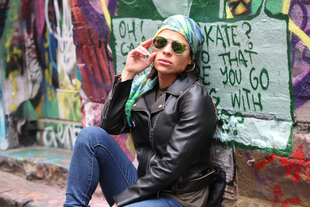 woman in black leather jacket and blue denim jeans wearing green knit cap sitting on concrete