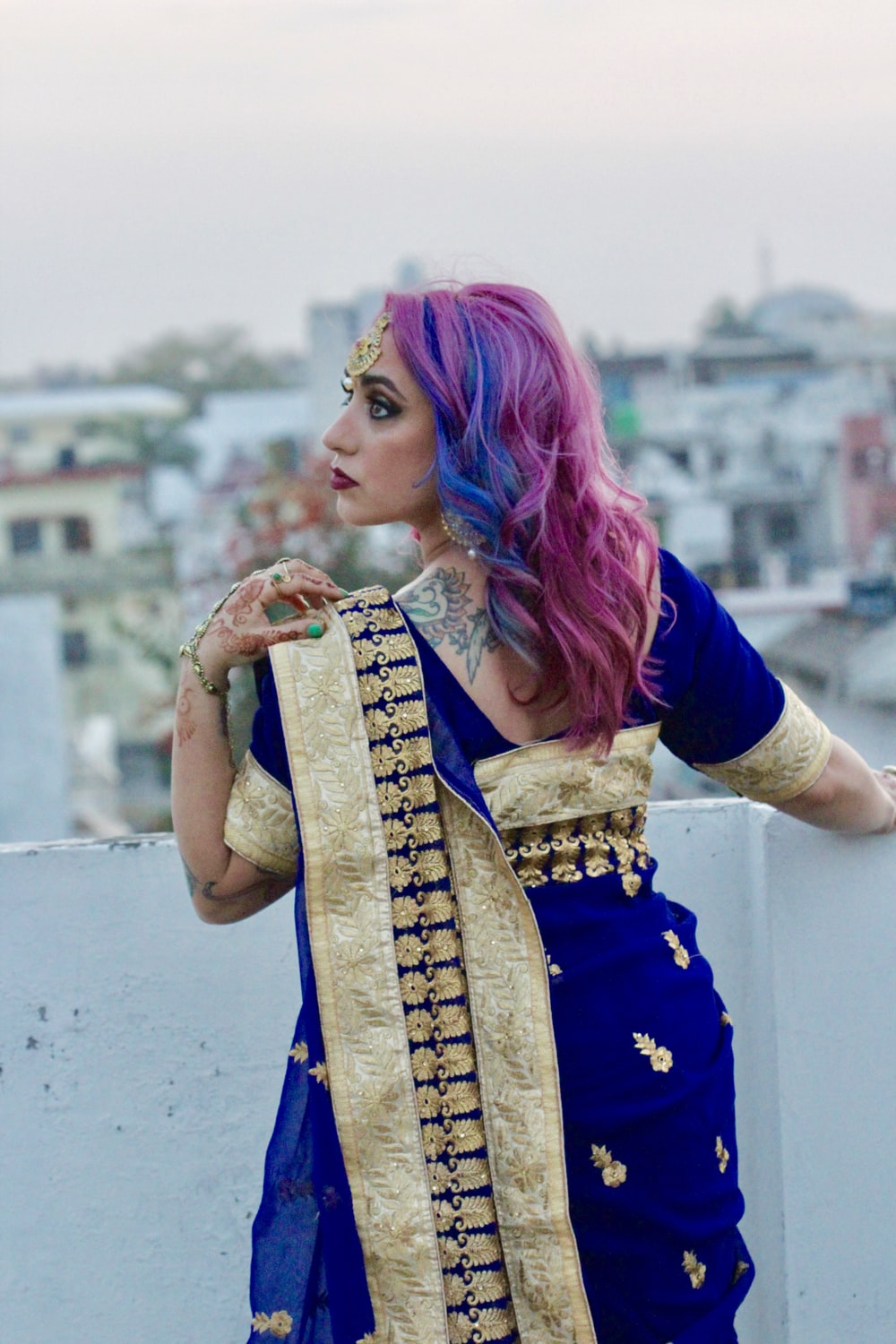 woman in blue and gold sari standing and smiling