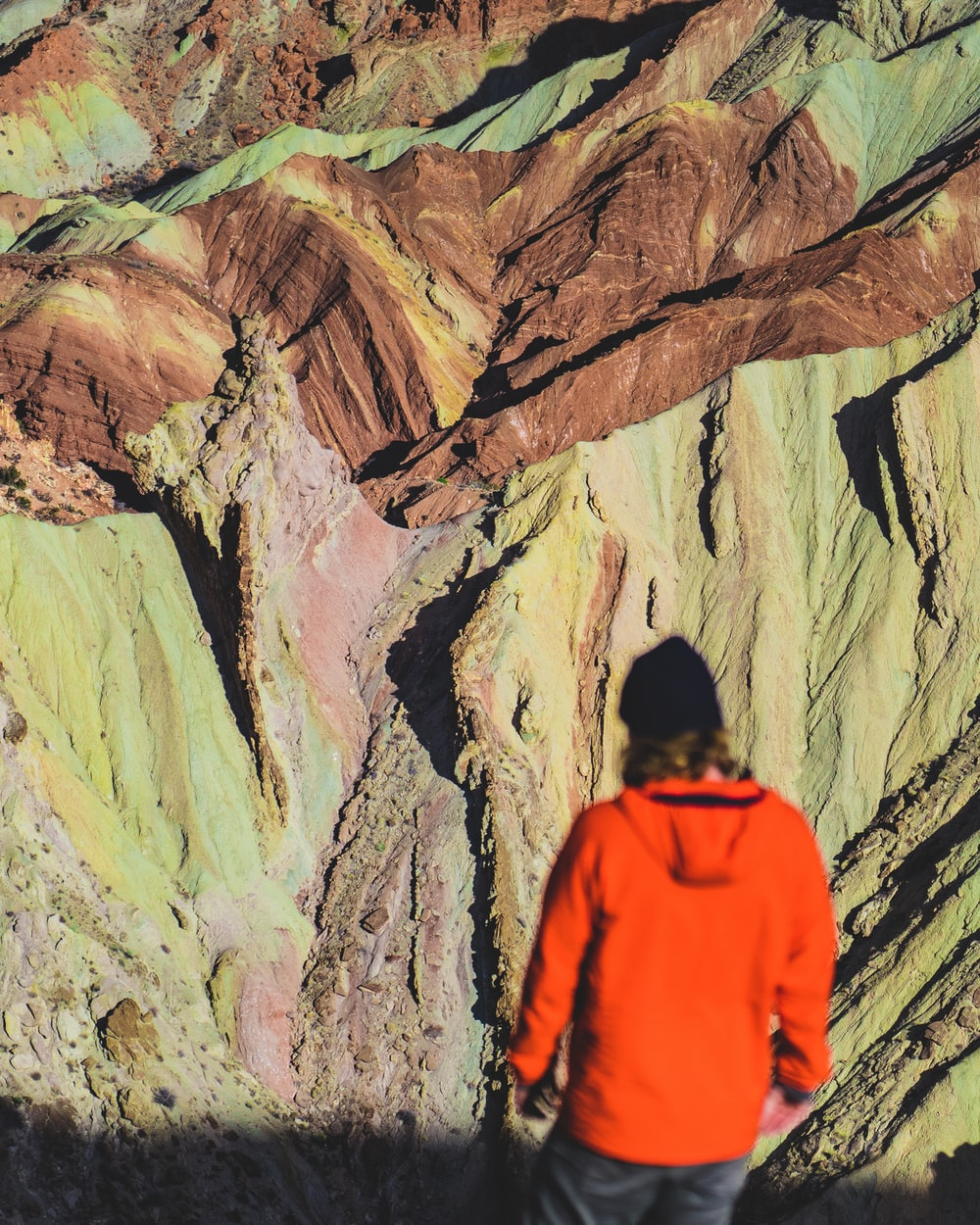 man in orange hoodie standing in front of brown and gray rock formation