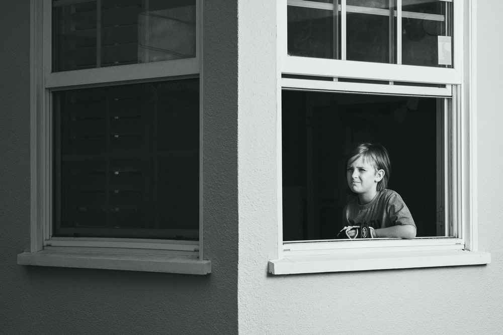 grayscale photo of girl in jacket looking out the window