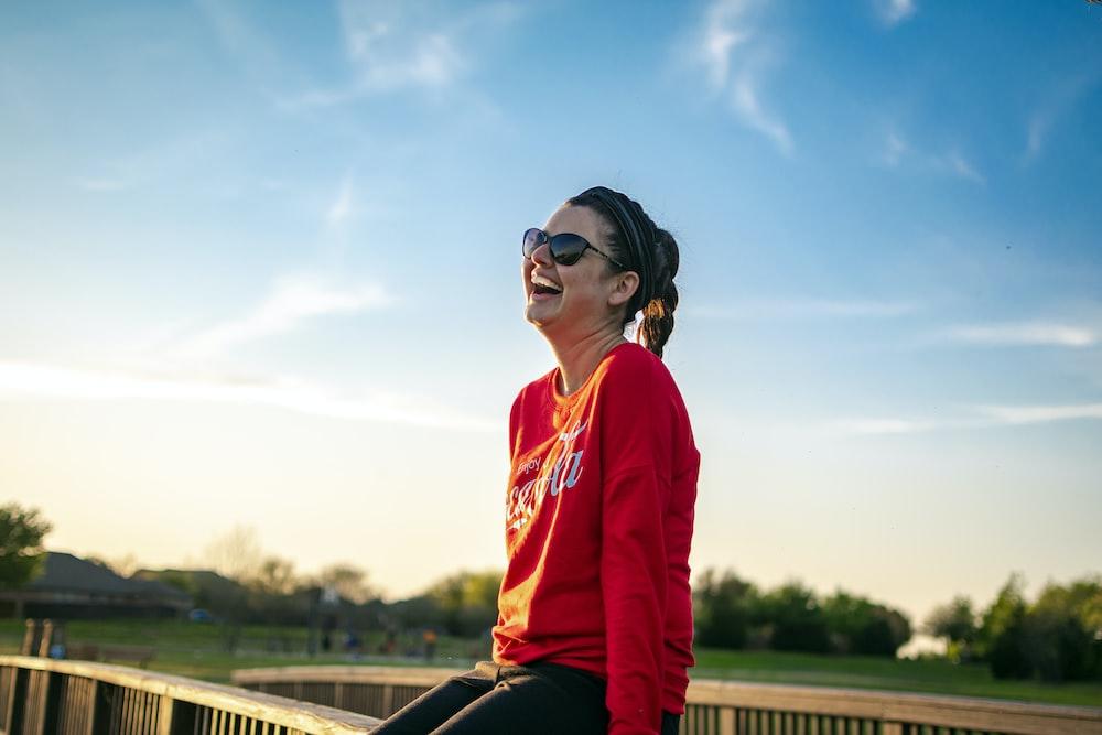 woman in red hoodie wearing black sunglasses