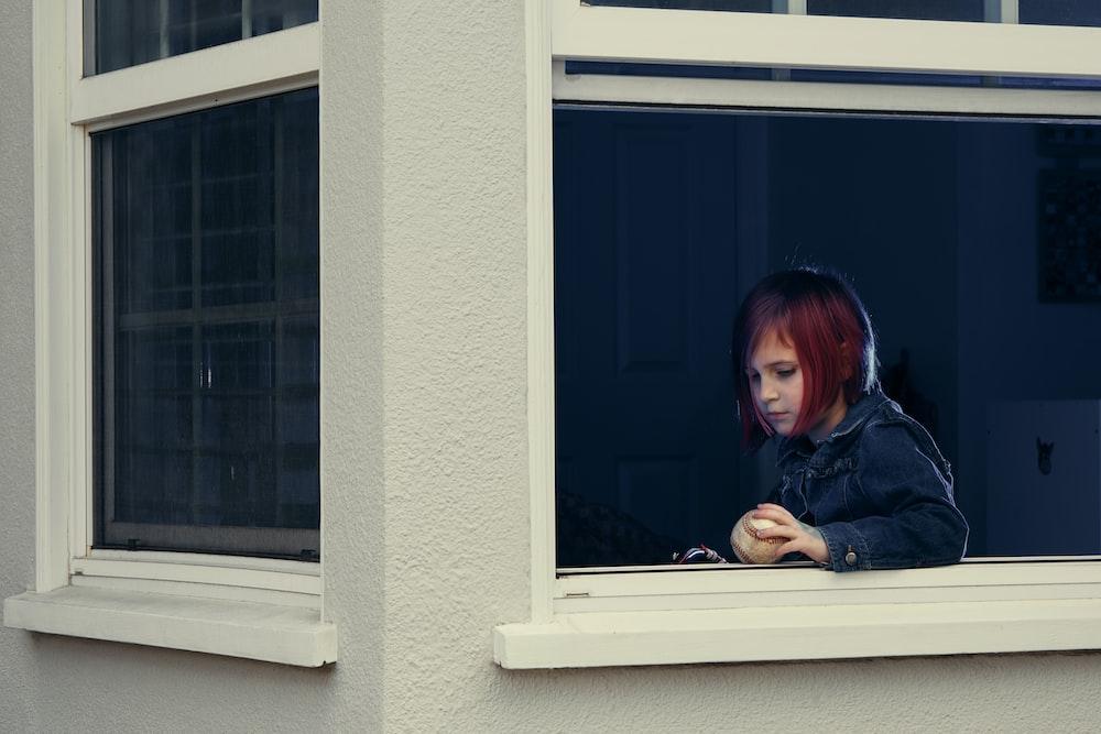 woman in black jacket sitting beside window