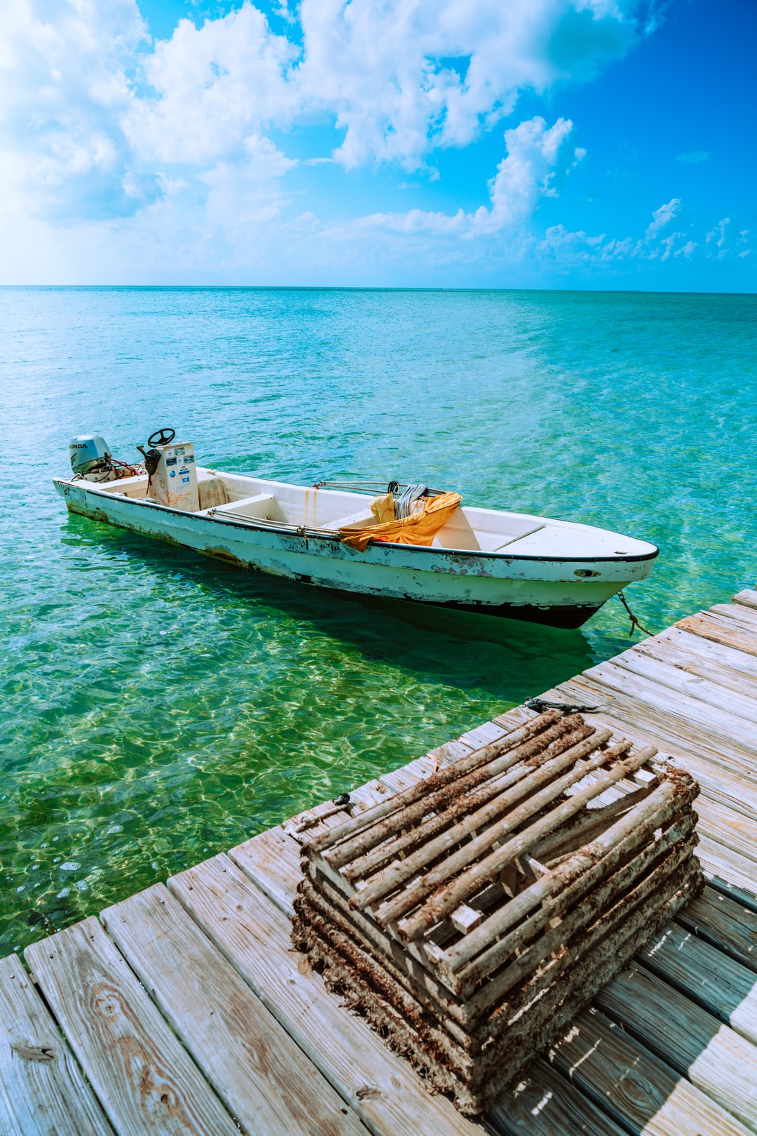 Small motor boat at a dock with a wooden crab trap.