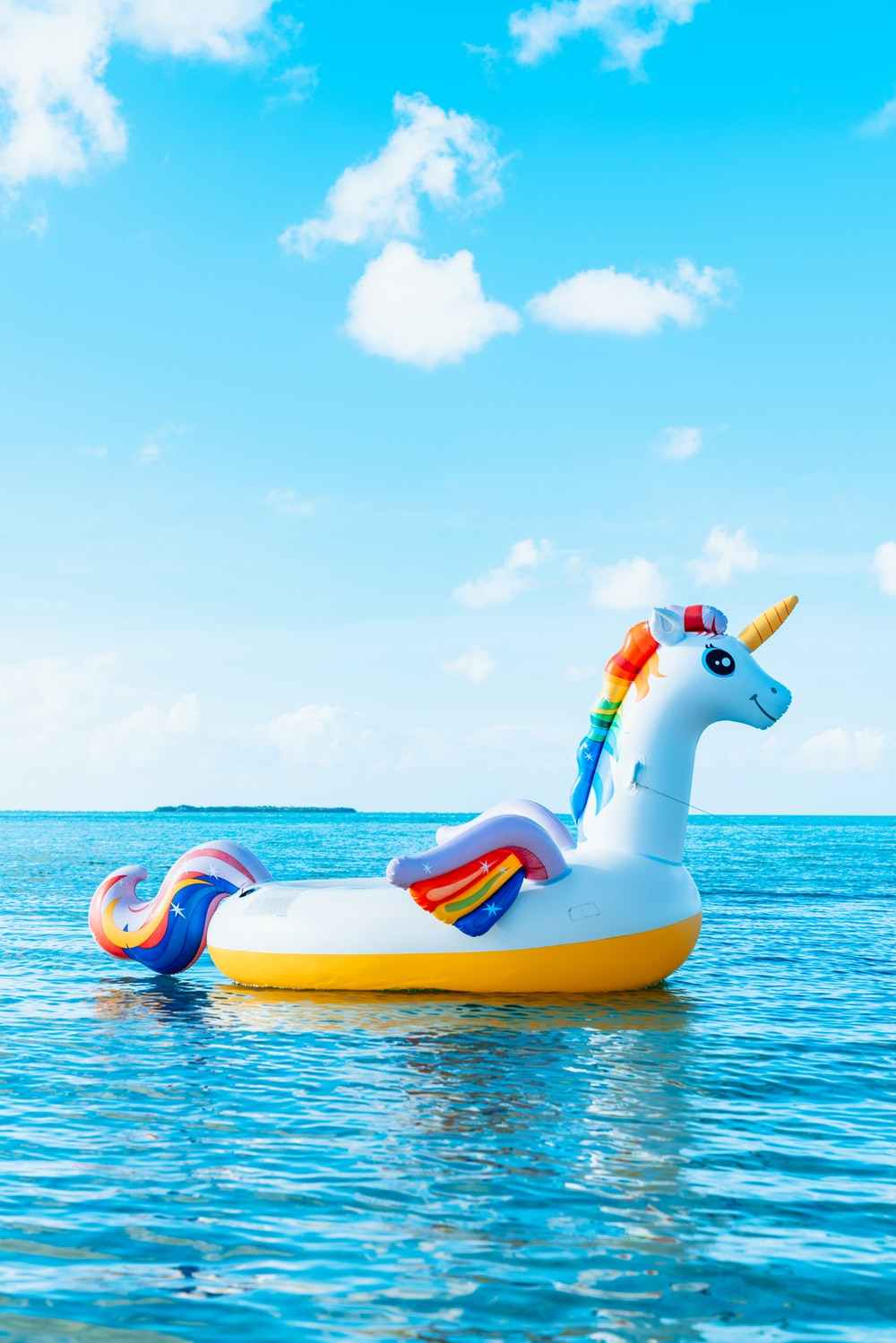 yellow and blue inflatable duck on blue sea under blue sky during daytime