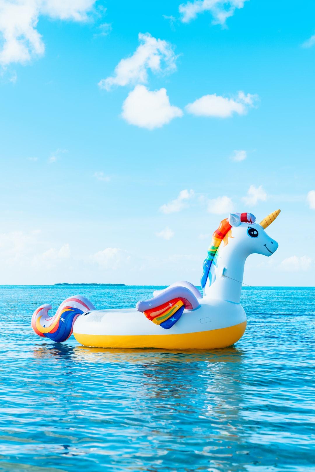 Rainbow unicorn inflatable inner tube in tropical island ocean water.