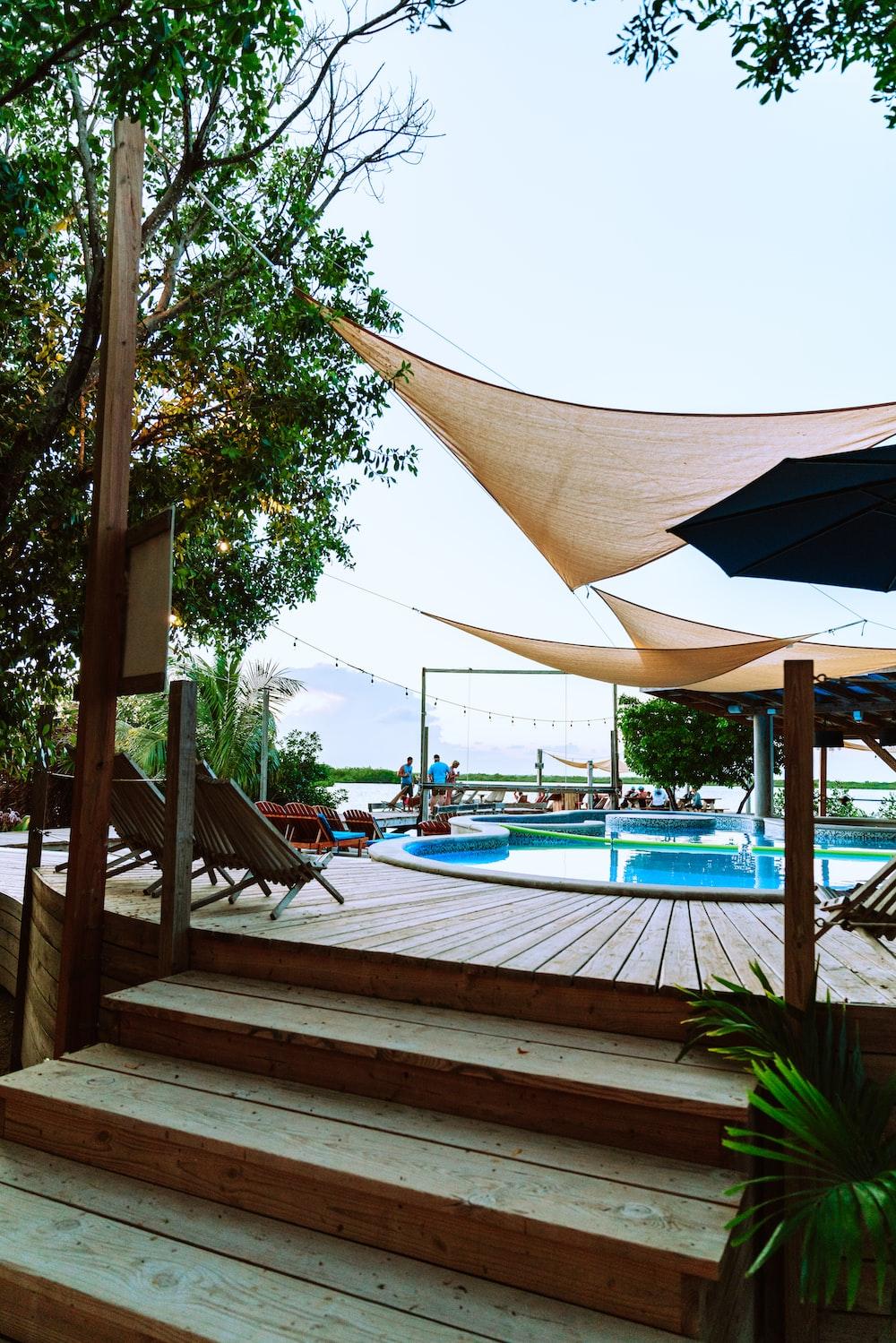 brown umbrella near swimming pool