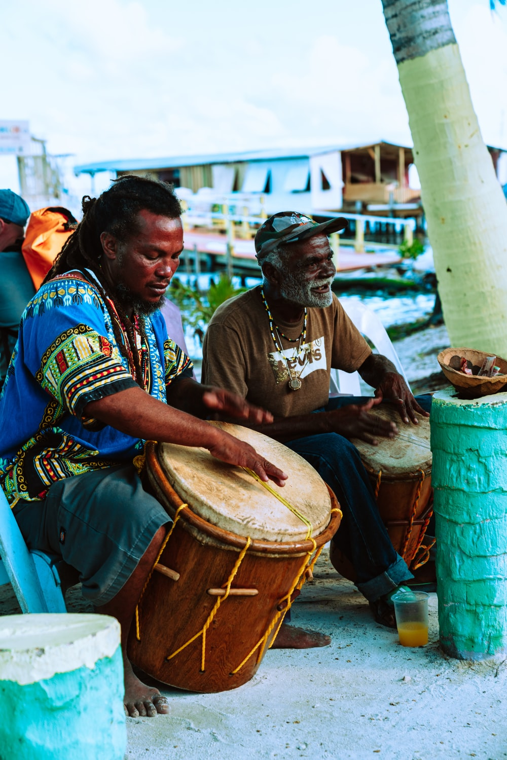 man in brown shirt playing drum