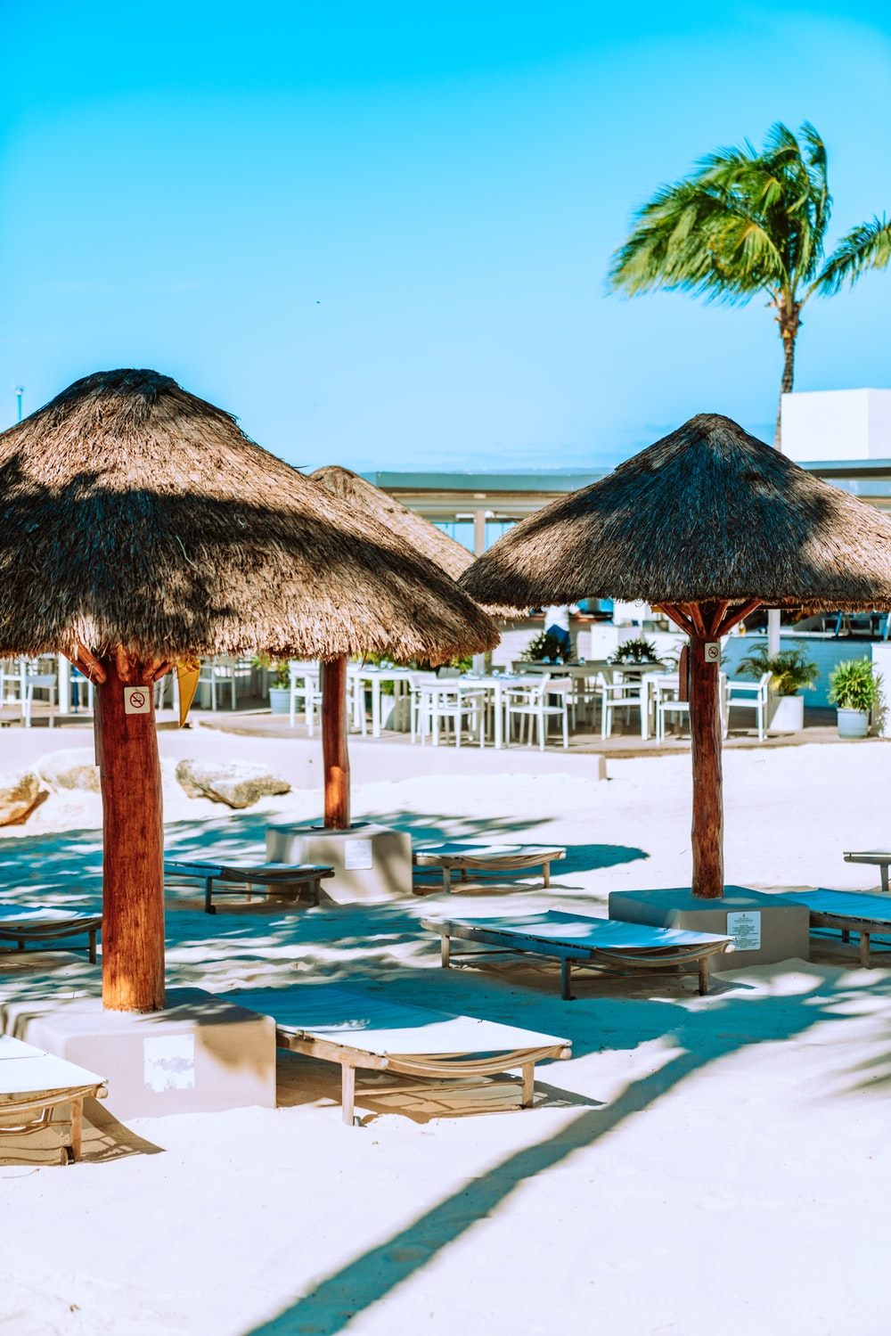 brown wooden beach lounge chairs near swimming pool during daytime