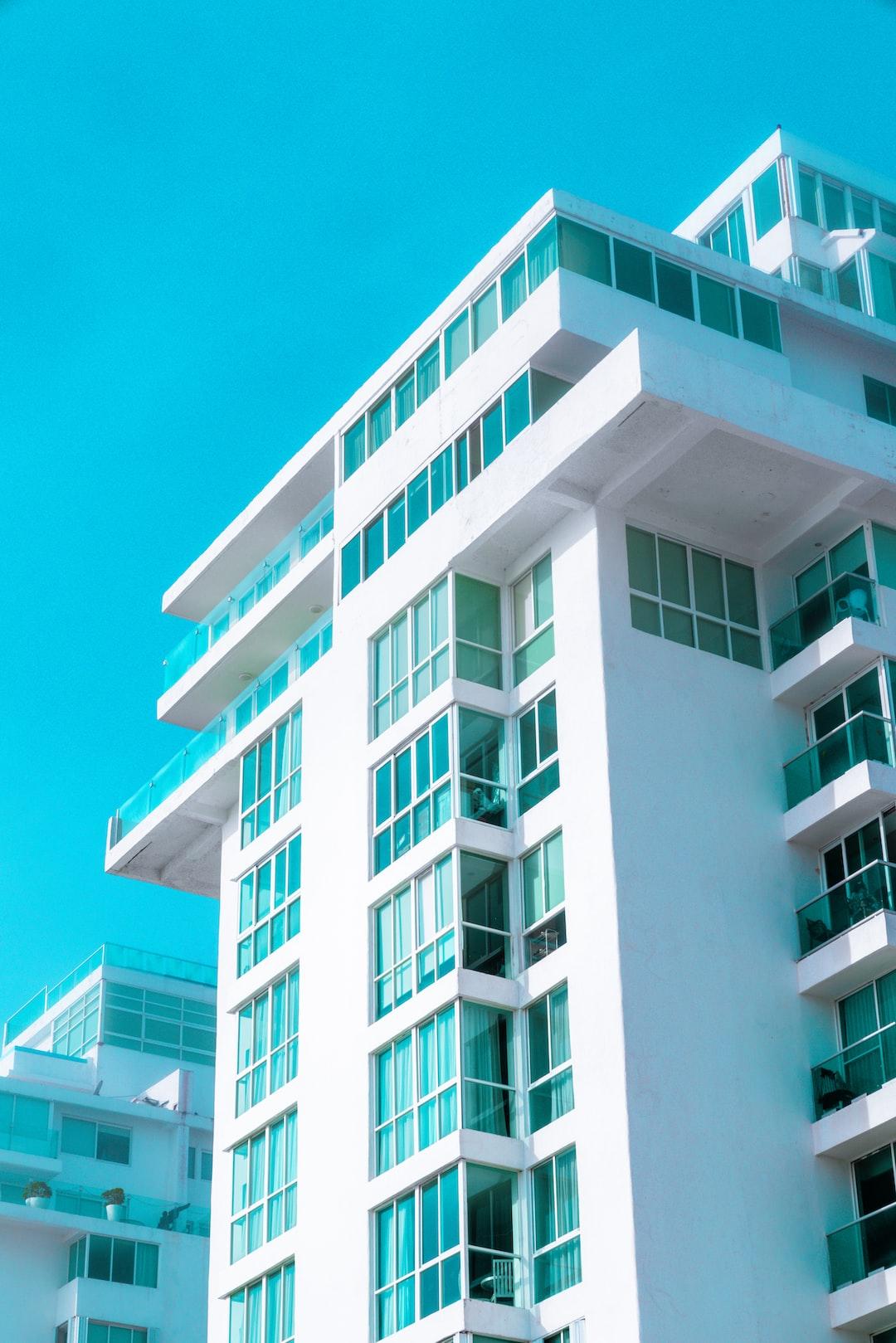 Modern white hotel building with teal windows—ÓLEO Resort.