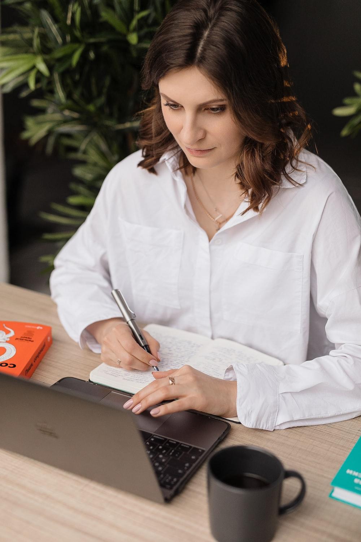 woman in white dress shirt using black laptop computer
