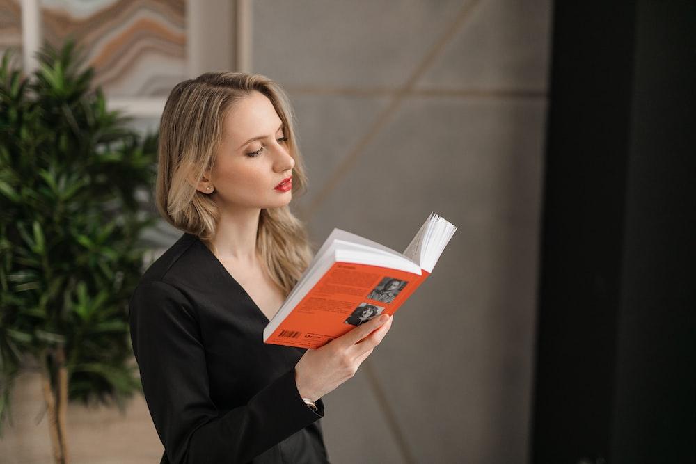 woman in black blazer holding orange book