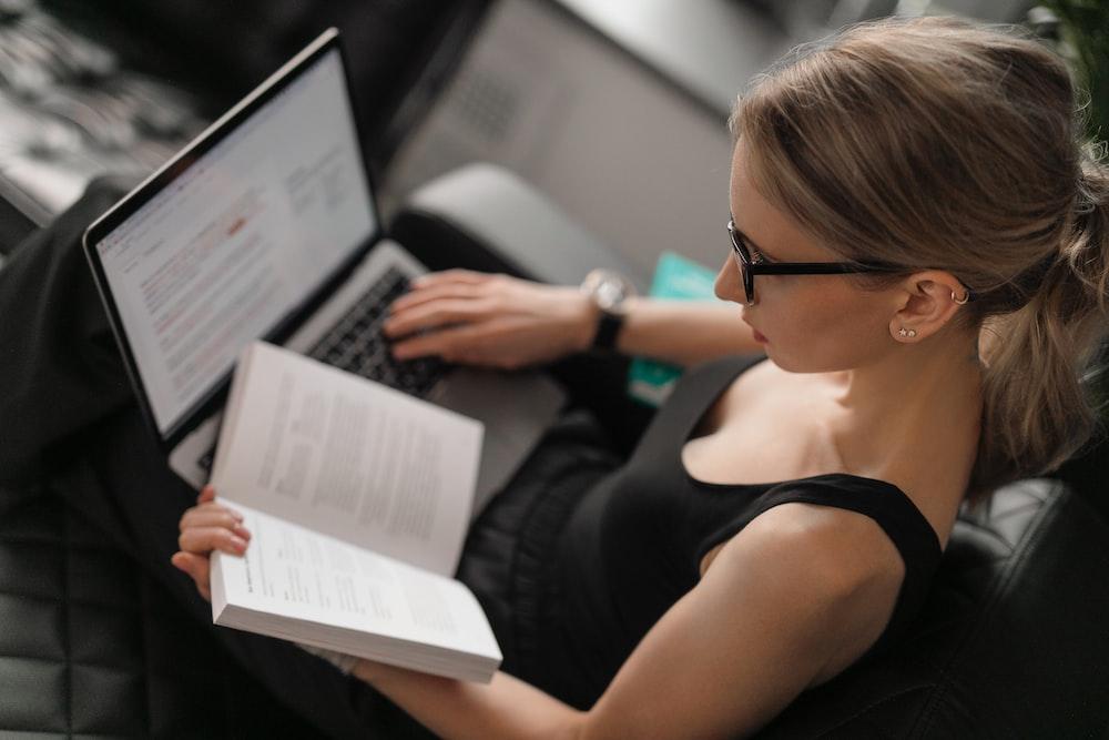 woman in black tank top using macbook pro