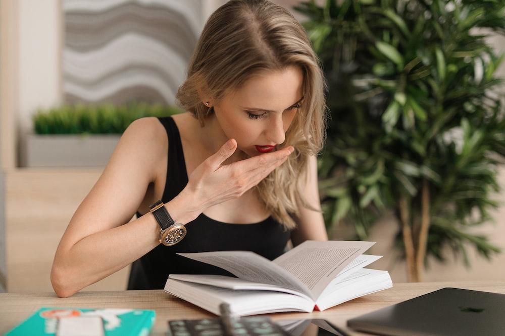 woman in black tank top reading book