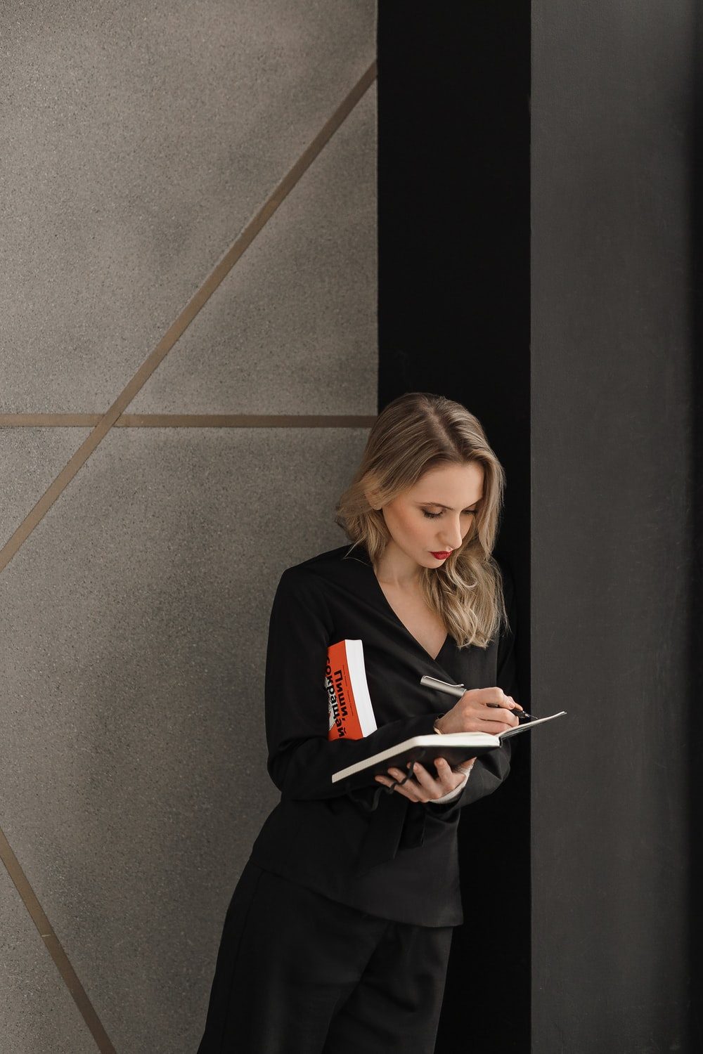 woman in black long sleeve shirt holding white tablet computer