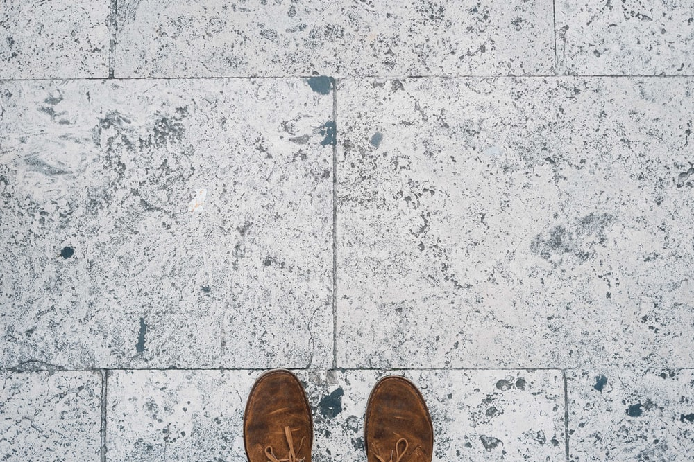 person in brown shoes standing on gray concrete floor