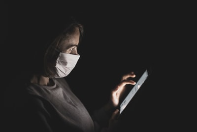 person weras white mask to protect from coronavirus pandemic teams background