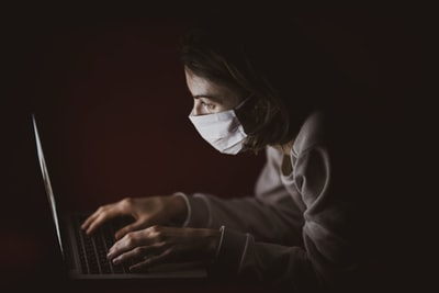 woman in black long sleeve shirt using laptop computer pandemic teams background