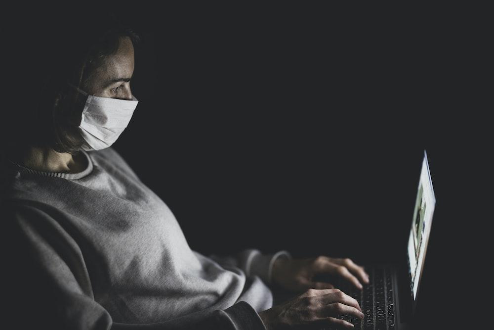 man in gray robe using laptop computer