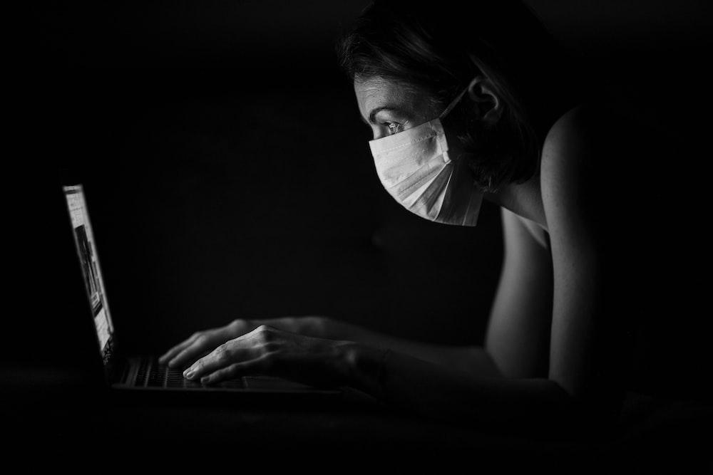woman in black framed eyeglasses using laptop computer