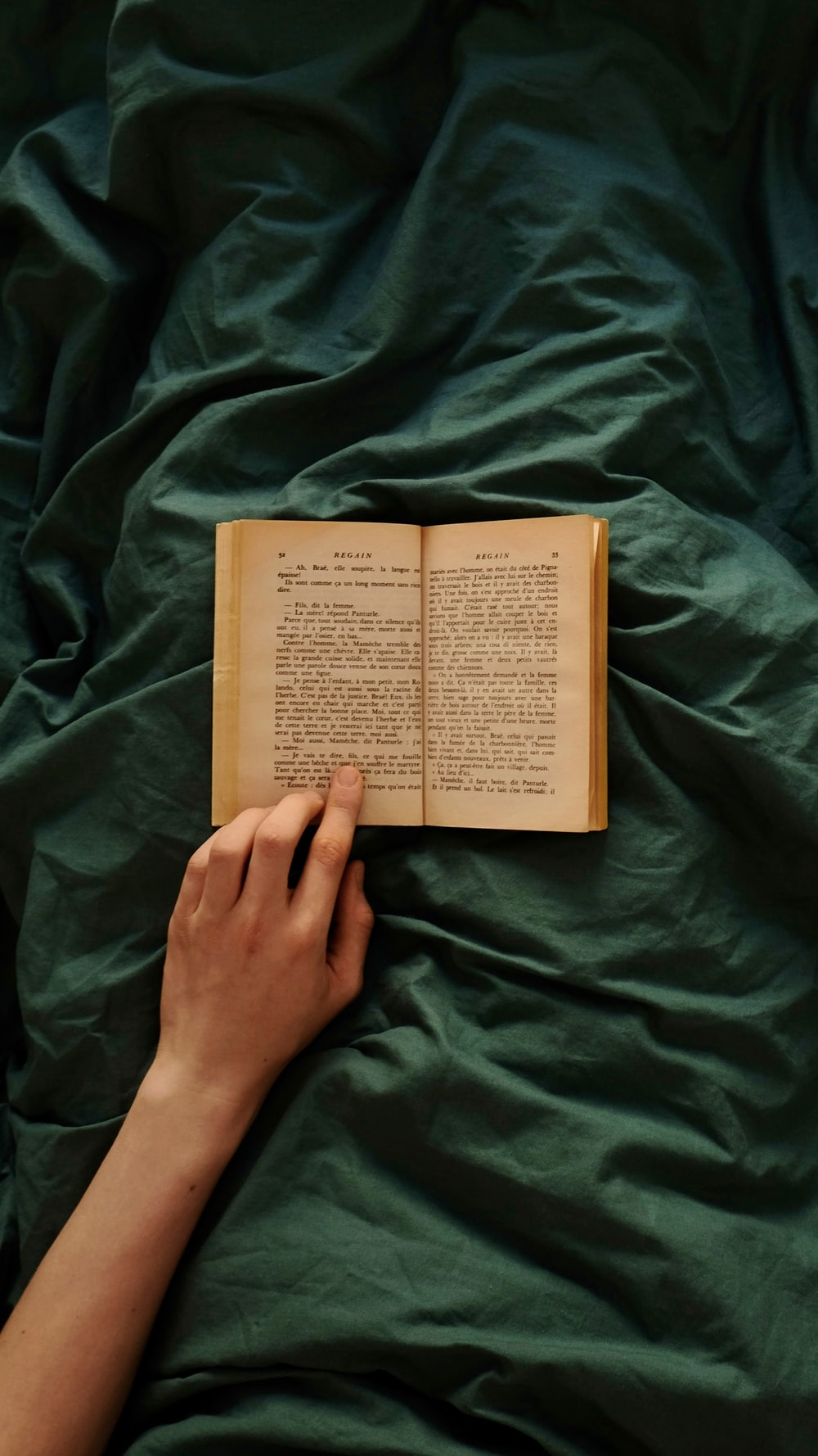 person holding brown book on green textile