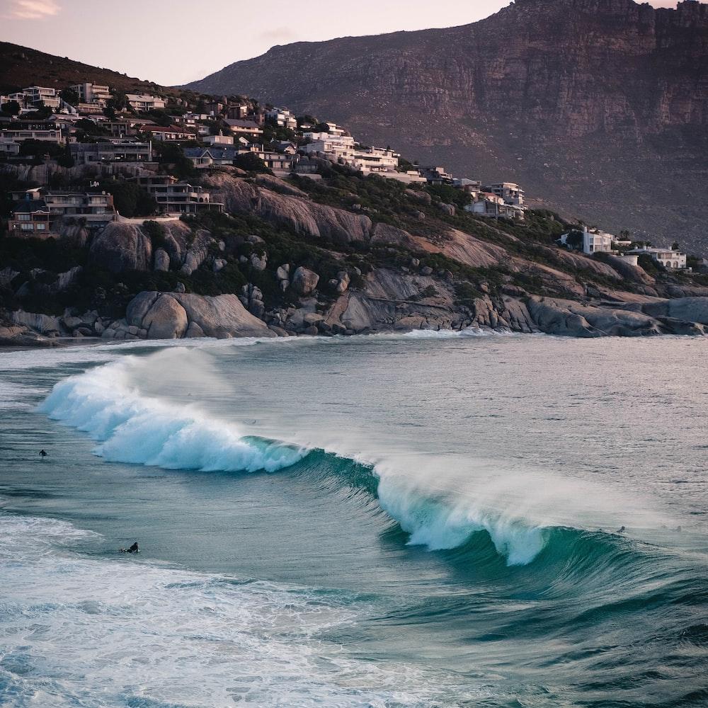 ocean waves crashing on rocky shore during daytime
