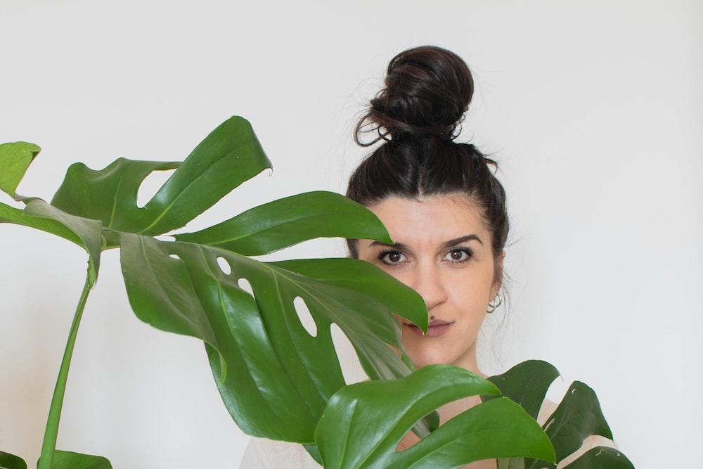 woman hiding behind green leaves