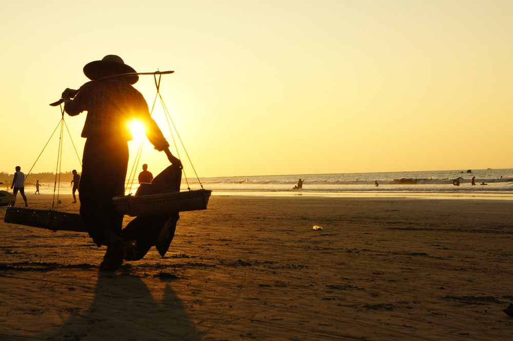 silhouette of man sitting on boat on beach during sunset