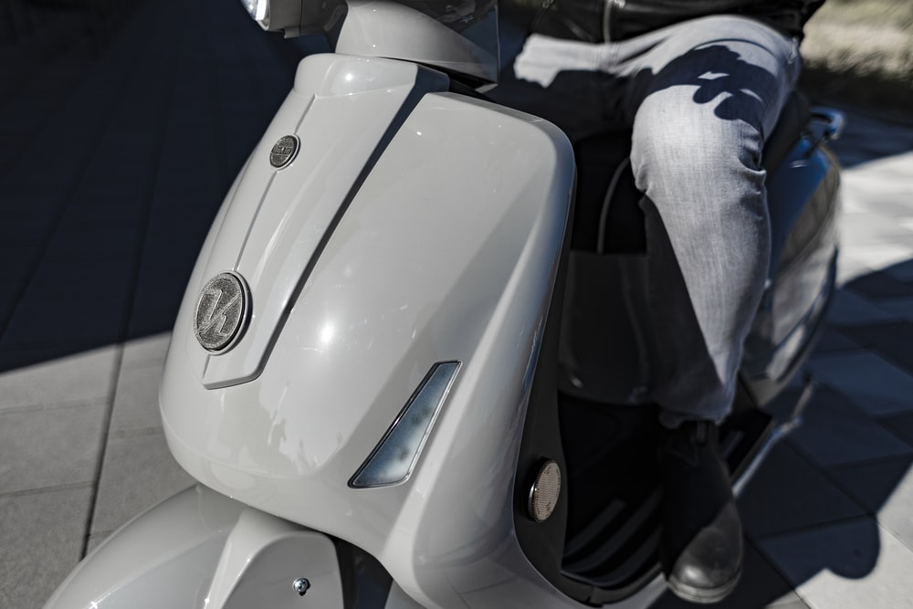 person in blue denim jeans sitting on white motorcycle