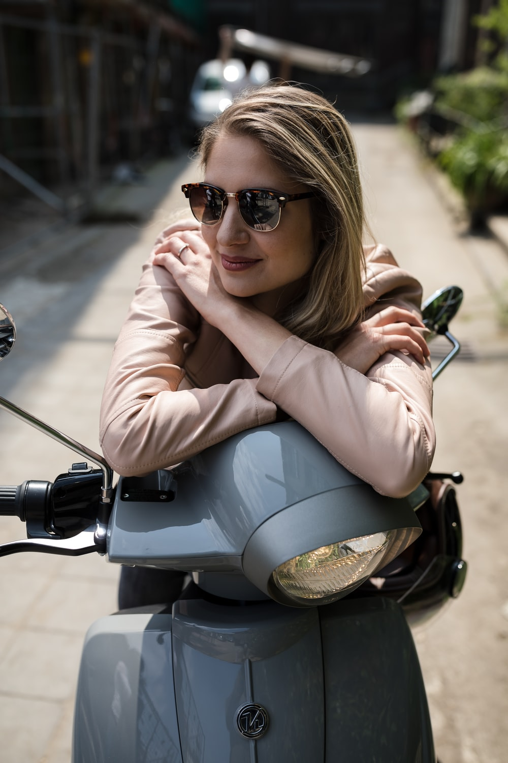 woman in brown leather jacket and black sunglasses sitting on black motorcycle