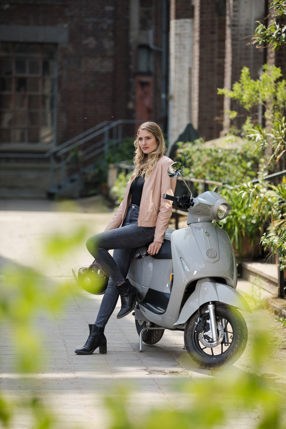 woman in black jacket and black pants riding on gray motor scooter