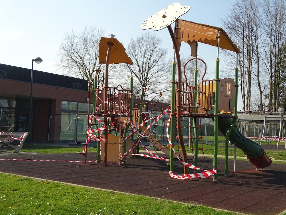 brown wooden swing on green grass field