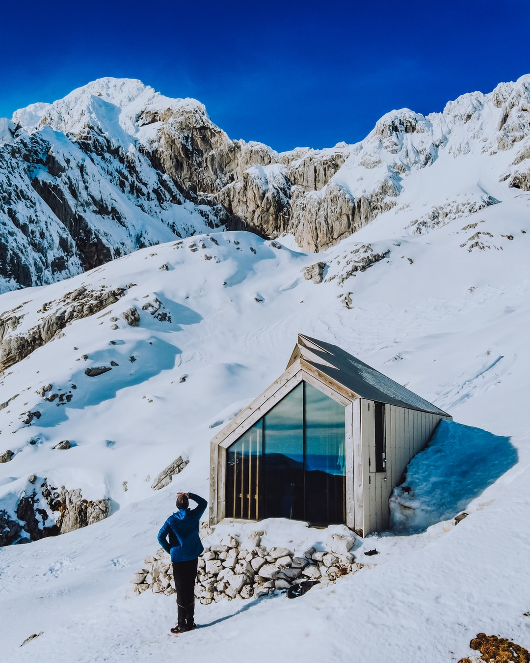 Man looking at the Skuta mountain in front of a bivouac shelter.