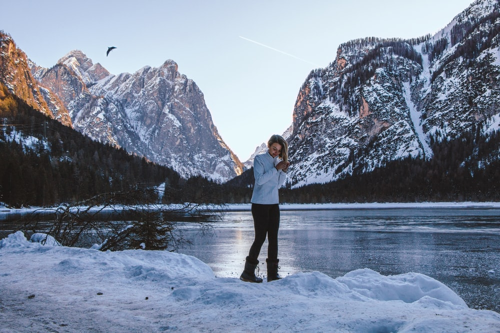 man in white jacket and black pants standing on snow covered ground near body of water