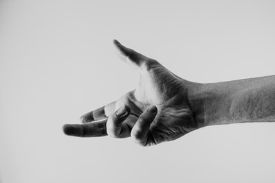 grayscale photo of persons hand hand zoom background