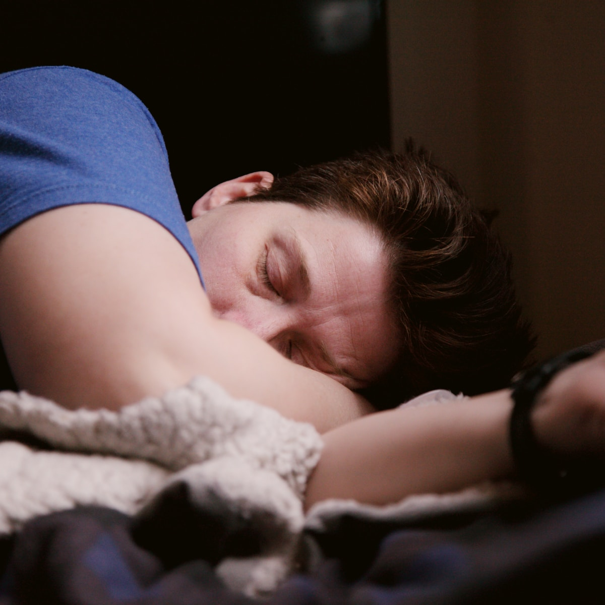 woman in blue shirt lying on bed