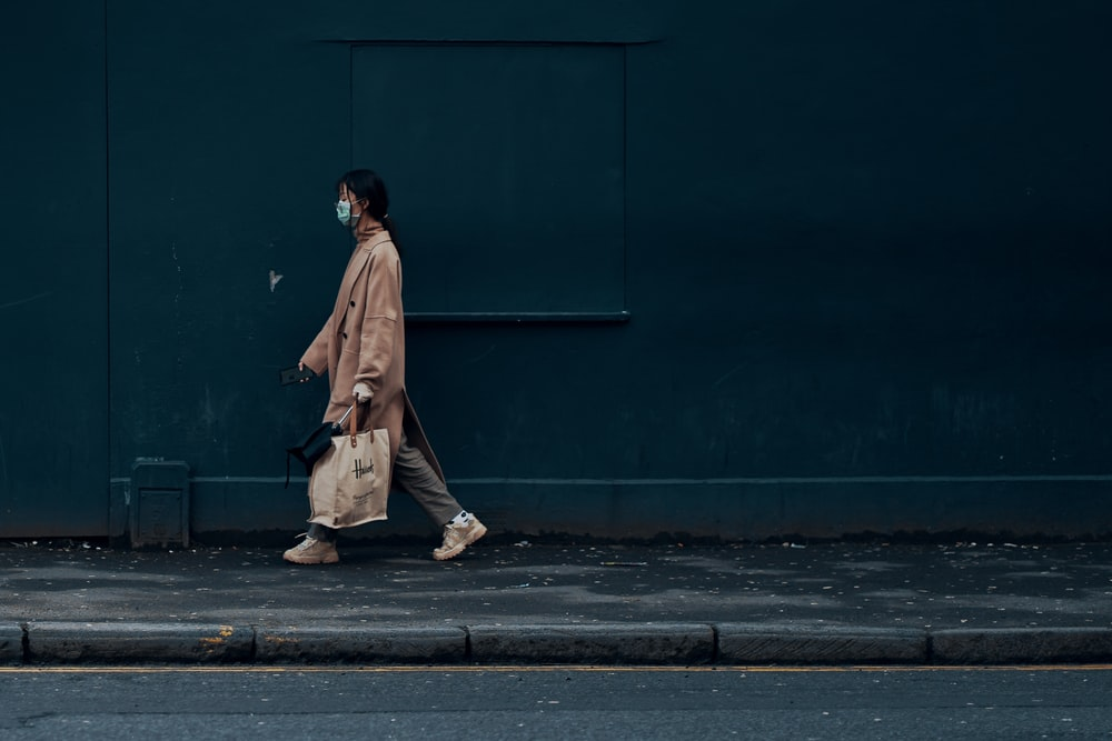 man in brown coat standing beside blue wall
