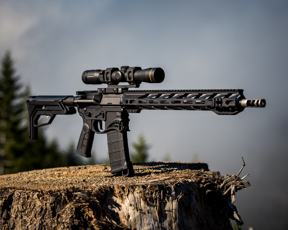 black airsoft rifle on brown grass field