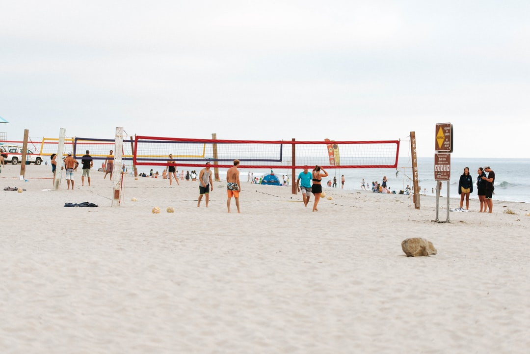 A lively game of beach volleyball, with multiple colored nets.