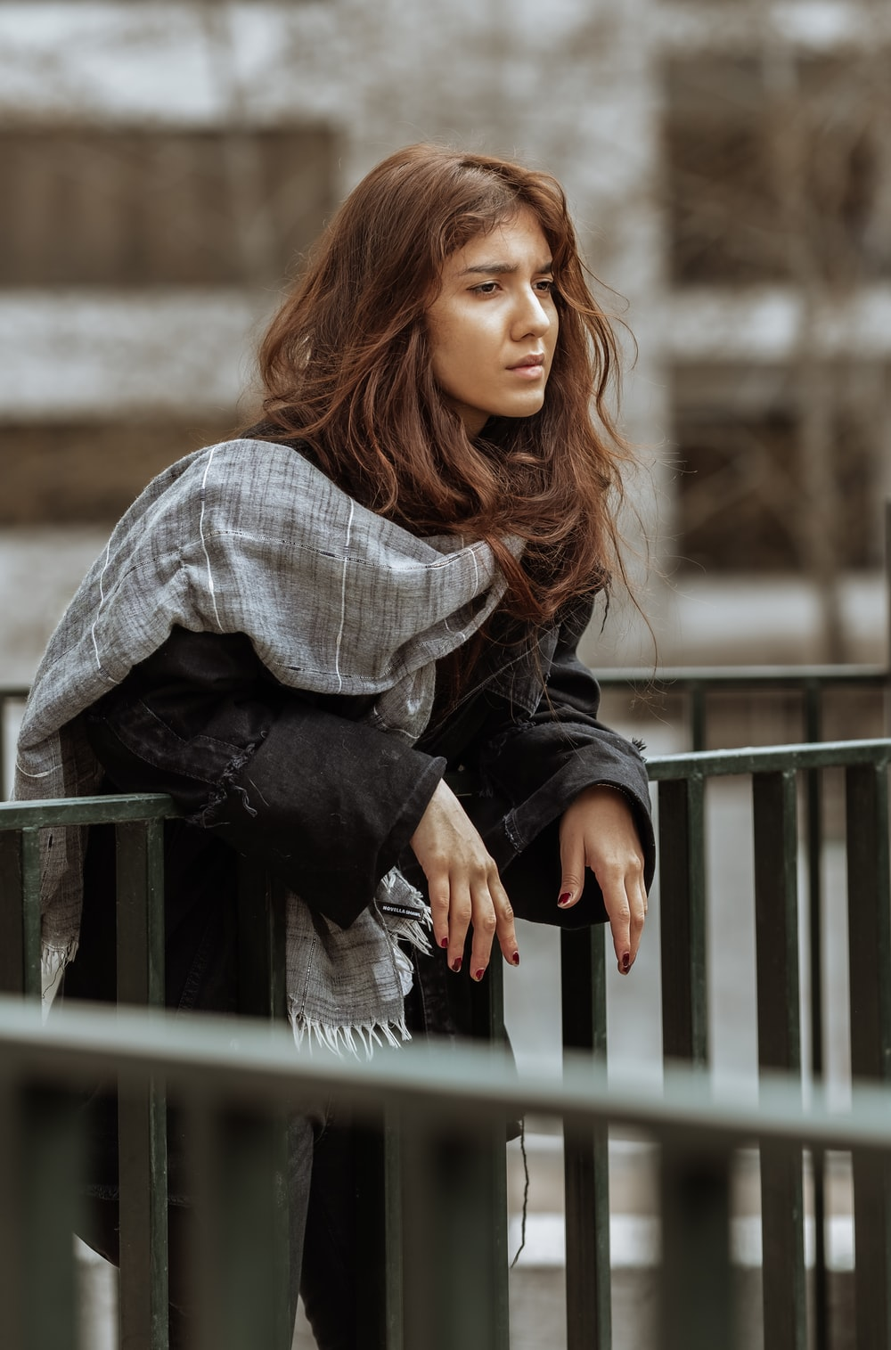woman in white and black plaid long sleeve shirt and black pants sitting on gray wooden
